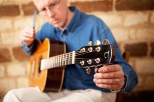 Мужчина настраивает гитару